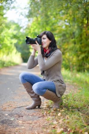 happy seasonable: beautiful female photographer takes photo outdoor