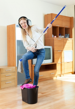 Happy housewife in headphones washing floor with mop in living room at home photo