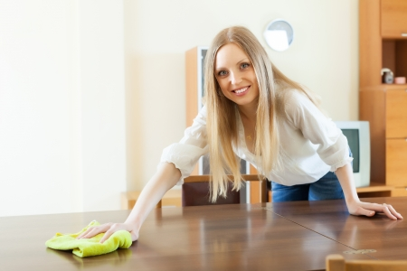 Happy  long-haired woman wiping the dust from table at home photo