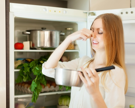 frowy: Long-haired woman  holding foul food near   refrigerator Stock Photo