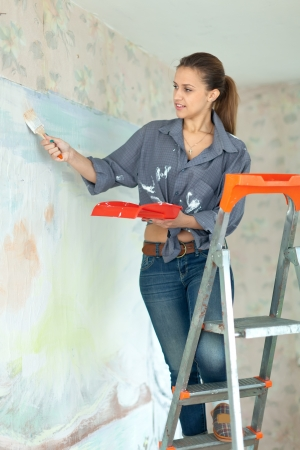 flat brush: Happy girl paints wall with brush at home
