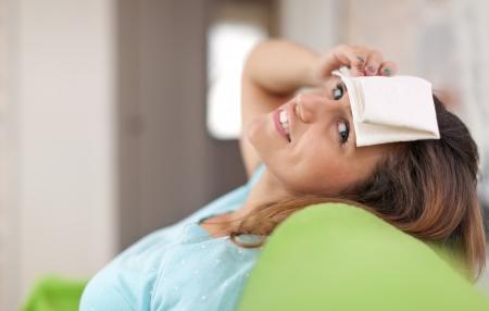 woman having  headache holding towel on her head