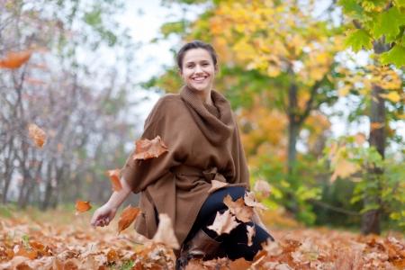 happy seasonable: Girl throws maple leaves in autumn park