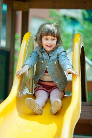 Feliz niña de dos años en la chaqueta en diapositiva en el patio de recreo