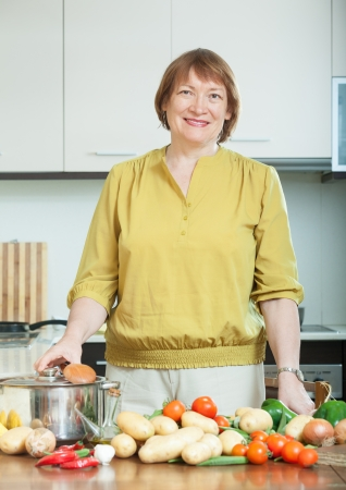 mature housewife  with pan and vegetables in home kitchen photo