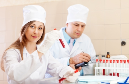 nurse and male doctor works with test tubes in clinic lab  photo