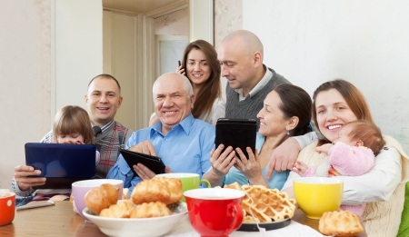 Happy family of three generations or group of friends with electronic devices over tea at home photo