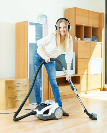 Happy blonde woman in headphones cleaning with vacuum cleaner on parquet floor at home photo
