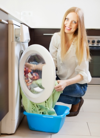 Happy long-haired woman loading clothes into the washing machine  at home Stock Photo - 20001923