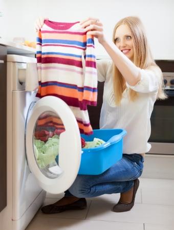 clothes washer: Mujer de pelo largo con el color de la ropa cerca de la lavadora en casa