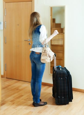 Long-haired girl with luggage looking in mirror near door in home photo