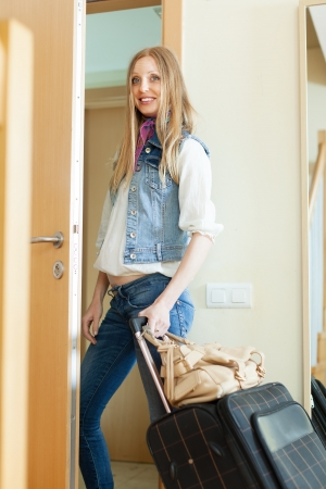 Long-haired girl with luggage leaving her home photo