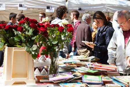 BARCELONA, CATALONIA - APRIL 23: Saint George day (Sant Jordi) in April 23, 2013 in Barcelona, Catalonia. Books and red roses - symbols of Sant Jordi feast in Catalunia