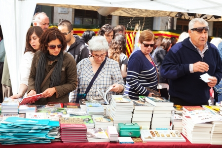 BARCELONA, SPAIN - APRIL 23: Books on street stalls  in Saint George day in April 23, 2013 in Barcelona, Spain. Saint George is the patron saint of city, ​​decided to give red roses and books