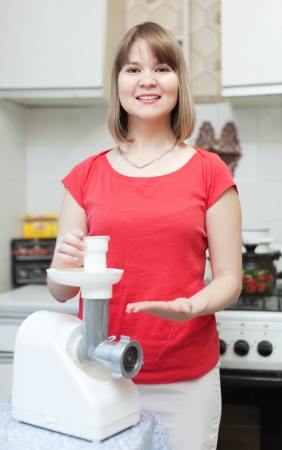 eastward: Woman with electric meat chopper in kitchen  Stock Photo