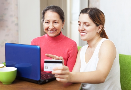 adult daughter helps the mother buying online with laptop and credit card  in living room Stock Photo - 20081899