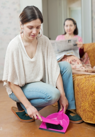 Clean up young woman, while her mature mother reads newspaper on the sofa at home photo