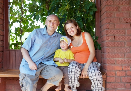 Happy parents with child sits on bench in veranda Stock Photo - 20144950