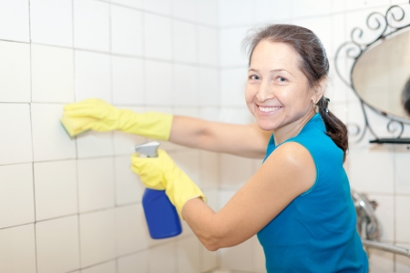 Smiling  mature woman cleans tile with sponge in bathroom  photo