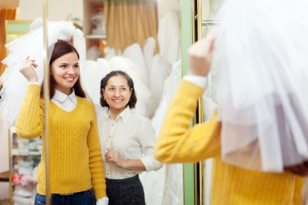 Mature mother  with daughter chooses wedding outfit at shop of wedding fashion photo