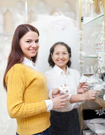 bride chooses bridal accessories at wedding store. Consultant helps her photo