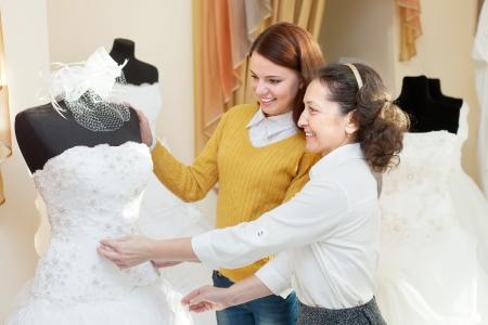 bridal gown: Mujer ayuda a la gitl elegir vestido de novia en la tienda de moda nupcial. Centrarse en madurez Foto de archivo