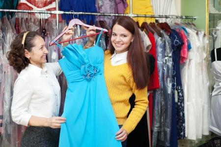 Happy women chooses blue dress at shop of clothes photo
