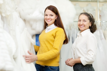 furskin: Mature woman with bride chooses white bridal clothes at wedding store