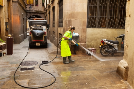 BARCELONA, SPAIN - JUNE 1: Wet cleaning of ancient streets in June 1, 2013 in Barcelona, Spain.  Street sweeper cleaning with water old district of  city