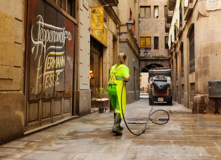 BARCELONA, SPAIN - JUNE 1: Wet cleaning of ancient streets in June 1, 2013 in Barcelona, Spain.  Street sweeper cleaning with water old district of european city