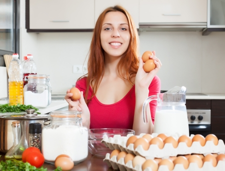 cheeful: Cheeful woman in red with eggs in home kitchen Stock Photo