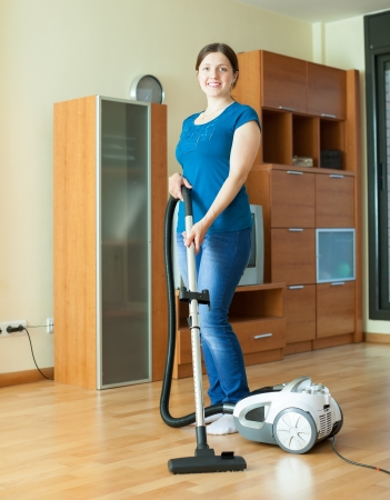 full length shot of woman cleans with vacuum cleaner at home photo