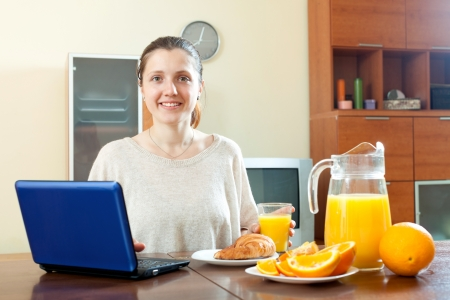 ordinary woman: Happy ordinary woman using laptop during breakfast at home