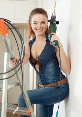 joven mujer sexy feliz con un mono con el taladro en la escalera en el interior