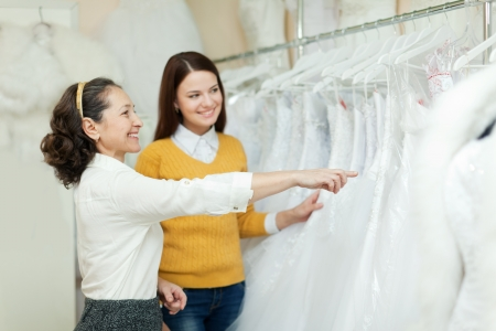 Shop assistant  helps the bride in choosing bridal dress at shop of wedding fashion photo