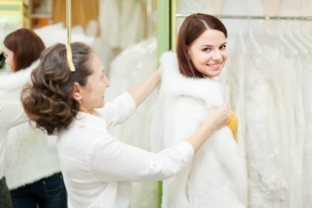 furskin: Female shop consultant helps bride chooses fur cape at shop of wedding fashion. Focus on girl
