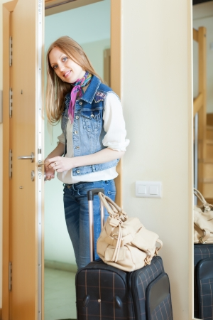 woman with luggage loocking door and leaving her home photo