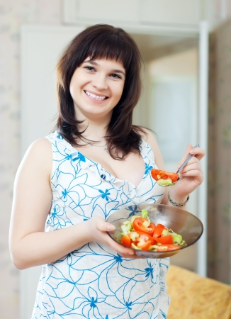 ordinary woman: positive  ordinary woman plate of  tomatoes salad at home Stock Photo