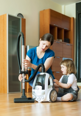 teaches: Woman teaches child to use the vacuum cleaner in living room