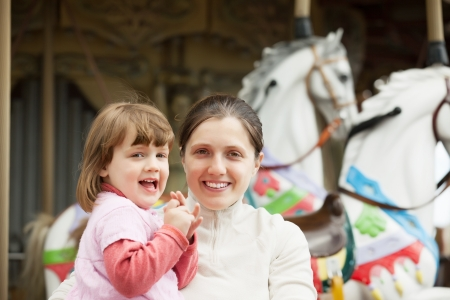 carrousel: happy mother with baby girl against carousel