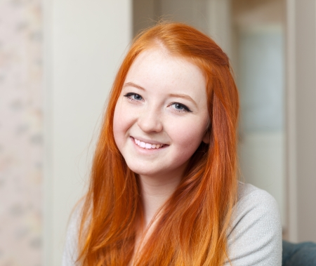 tenager: Portrait of smiling red-haired tenager girl in home