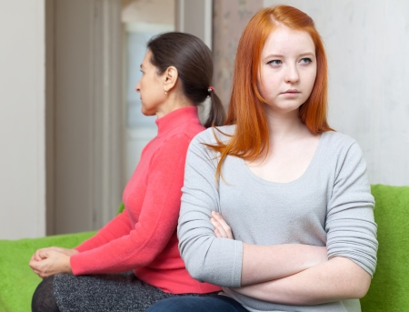fracas: Mature woman and teenager daughter having conflict at home. Focus on girl Stock Photo