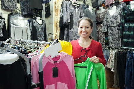 Woman  chooses clothes at fashionable shop photo