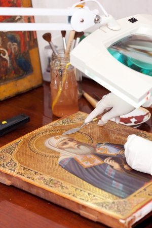 Art restorer working on the old icon at restoration workshop photo