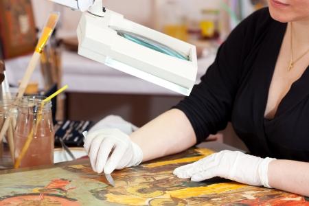 restoration: Restorer working on the ancient icon at restoration workshop