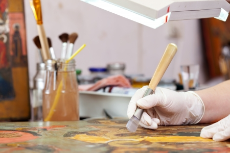 painting: Restorer working on the ancient Christian icon with agate burnisher
