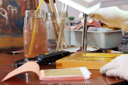 aureola: Iconographer works on new gilded icon with compasses at workshop Stock Photo