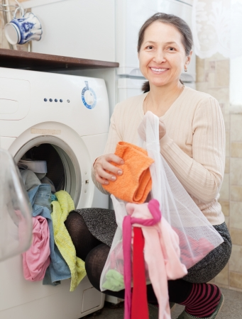 mature housewife loading the washing machine with laundry bag photo