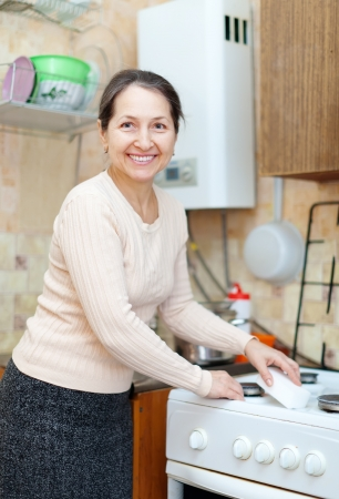 Happy mature housewife cleans the gas-stove  with sponge photo