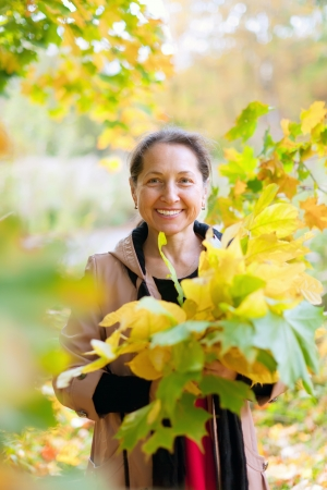 Outdoor portrait of mature woman in autumn with maple posy photo
